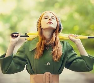 Девушка в зеленом плаще и с желтым зонтиком на улице