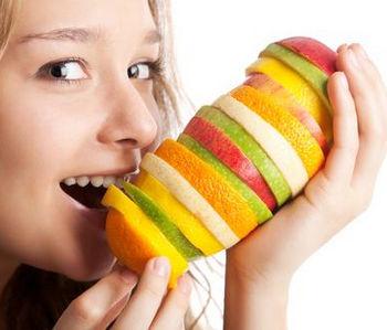Девушка кусает кучу нарезанных фруктов