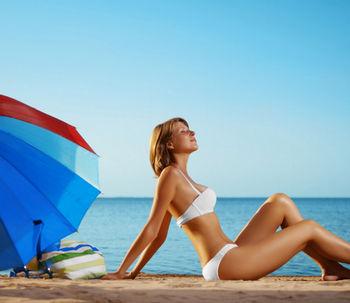 Женщина в белом купальнике принимает солнечные ванны