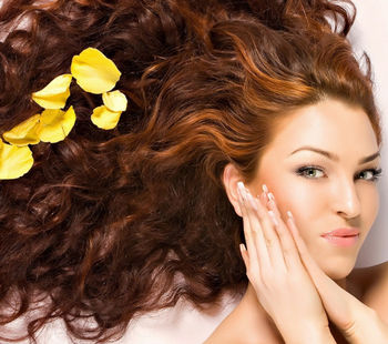 Кудрявая девушка с желтыми лепестками в волосах