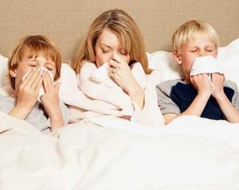 Мама и двое сыновей чихают в постели