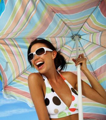 Счастливая девушка под большим солнечным зонтом