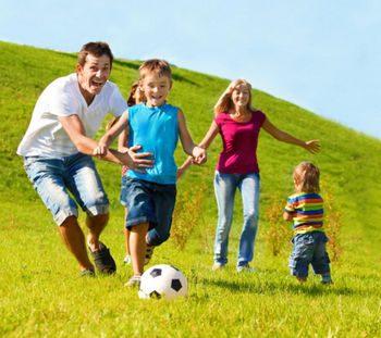 Семья играет с мячом на траве