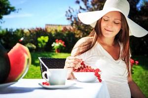 Беременная девушка в шляпе ест клюкву