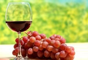 Вино в бокале и гроздь винограда