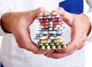 Врач держит большую стопку таблеток