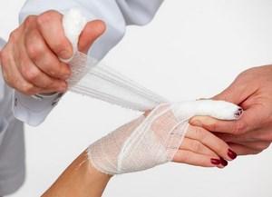 Врач перевязывает руку пациенту