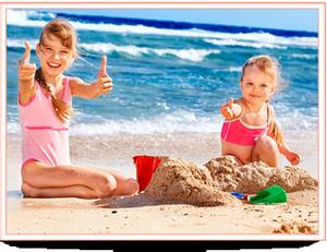 Две девочки строят замок из песка на море