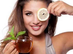 Девушка держит чай и лимон подставляет под глаз
