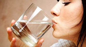 Девушка набирает в рот воду из стакана