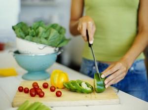 Девушка режет перец и другие овощи