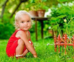 Девушка сидит на траве и смотрит в камеру