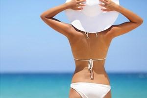 Девушка стоит под солнцем на море в купальнике