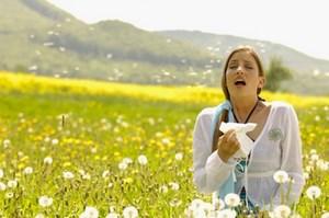 Девушка чихает на пооле с цветами