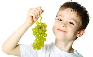 Мальчик держит в руках виноград