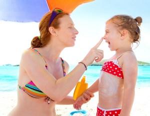 Мама мажет дочку кремом от солнца