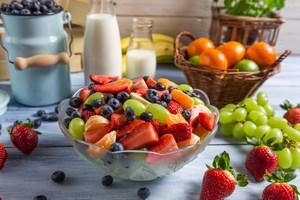 Салат из фруктов в миске и много фруктов на столе