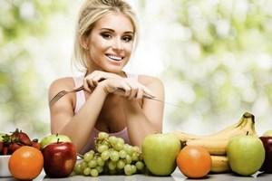 Девушка сидит с вилкой рядом с фруктами