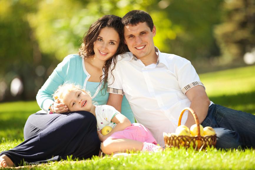 Happy family having a picnic in the green garden