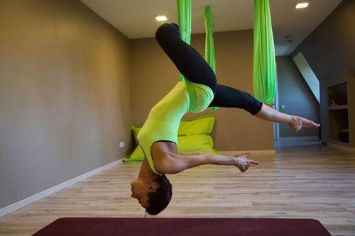 Девушка практикует антигравитационную йогу