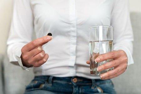 стакан воды и таблетка активированного угля в руках у женщины