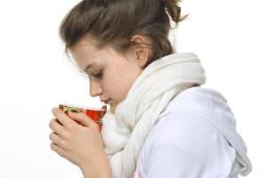Девушка в белом шарфе пьет из чашки